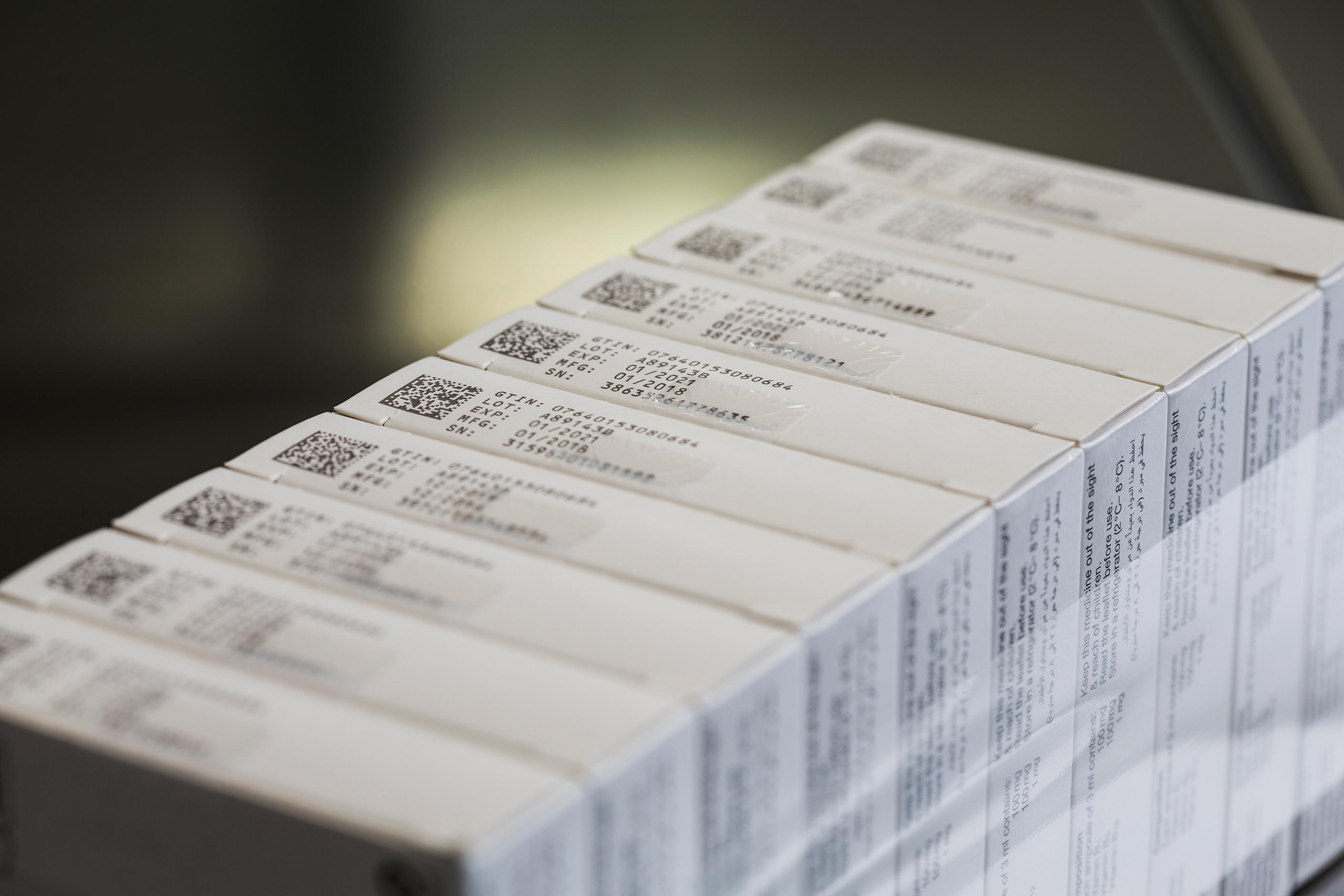 Gebündelte Medikamentenverpackungen mit Data Matrix Code und fünfzeiligem Klarschriftaufdruck.